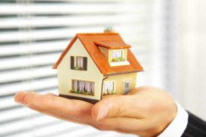 hand holiding a miniature house