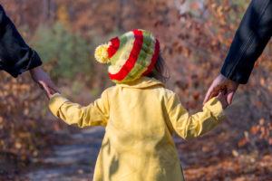 Little girl holding hands with mother and father