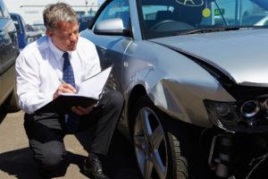 loss adjustor looking at damage to car